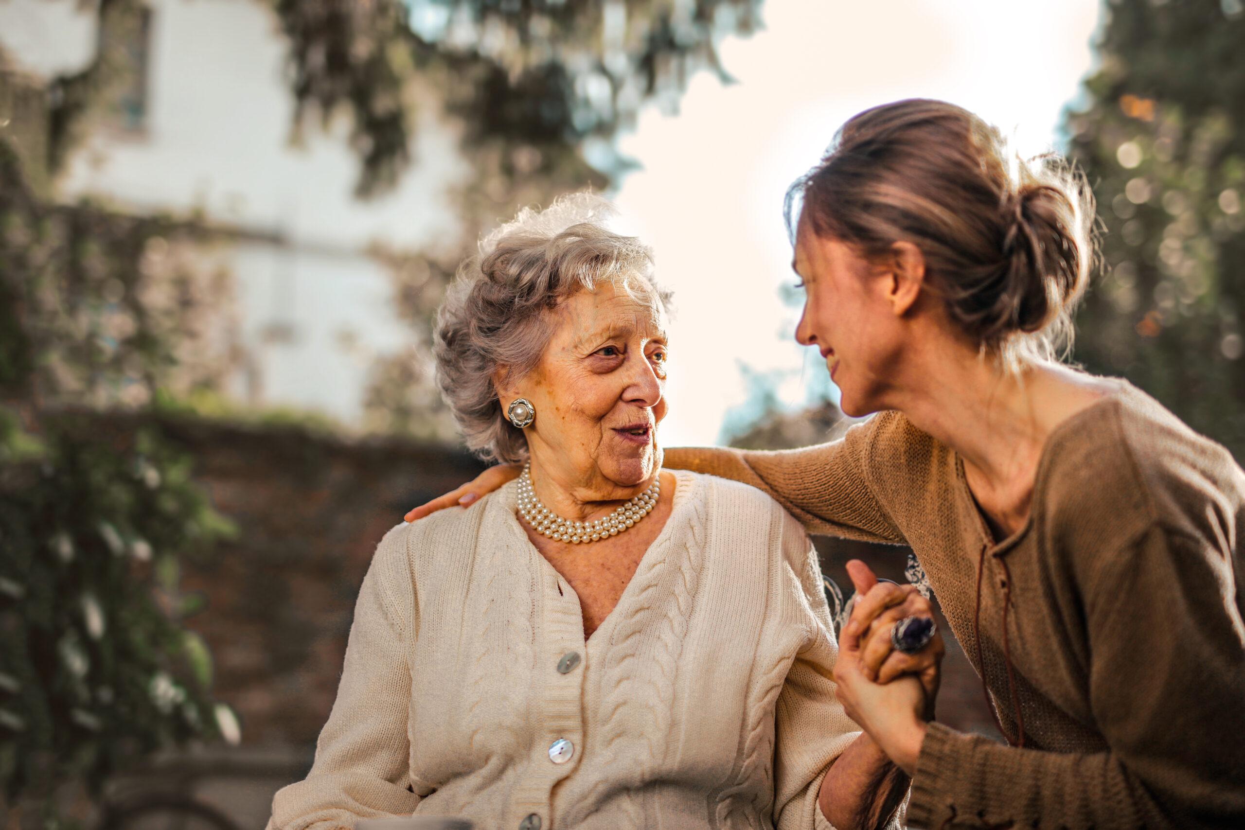 Starsza pani i opiekunka siedzą w ogrodzie